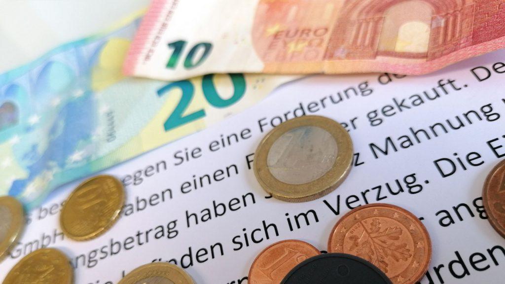 Kleingeld liegt auf einem Schreiben von einem Inkassounternehmen. Forderungen von Unternehmen über ein Inkassounternehmen können überzogen oder sogar unrechtmäßig sein.